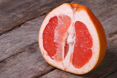 Sliced ripe grapefruit on an old wooden table closeup photo