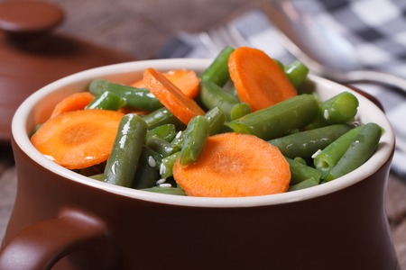 Green beans with sliced carrots in a pot for baking closeup   photo