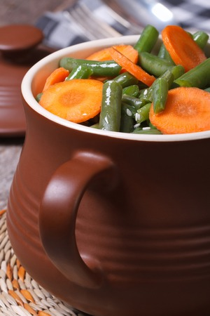 Green beans with sliced ??carrots in a pot close-up. vertical   photo
