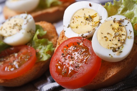 tasty useful sandwiches with boiled quail eggs, tomato and lettuce on the table. macro   photo