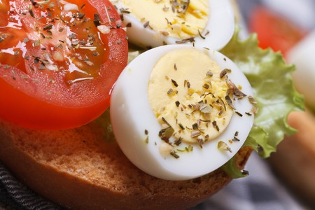 sandwich with boiled quail eggs, tomato and lettuce on the table. macro   photo