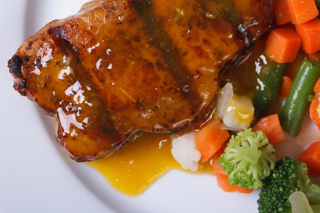 juicy piece of grilled meat with orange sauce and vegetables on a white plate. top view   photo