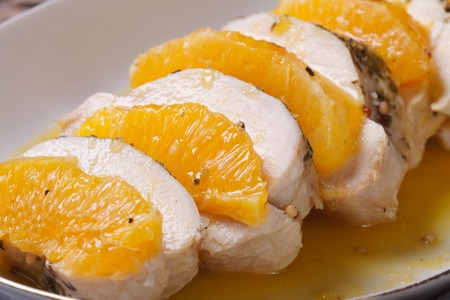 tasty chicken fillet with oranges and sweet and sour sauce on a white plate. horizontal. macro   photo