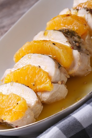 tasty chicken fillet with oranges and sweet and sour sauce on a white plate. vertical. close-up   photo