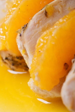 Sliced chicken with orange slices in sauce macro vertical  photo