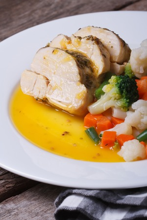 Sliced chicken with vegetables in orange sauce closeup. vertical   photo