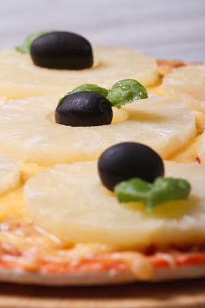 Pizza with pineapple and black olives on the table. macro. vertical  photo
