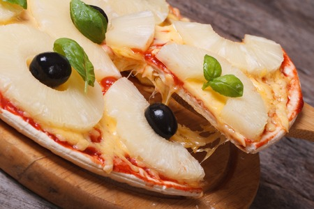 Slice of hot pizza with pineapple, cheese and black olives and basil on a paddle closeup  photo