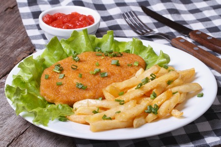 Schnitzel with french fries and sauce on a white plate on the old desk
