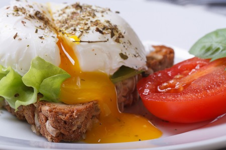 poach: open poached egg, tomato and bread on a plate