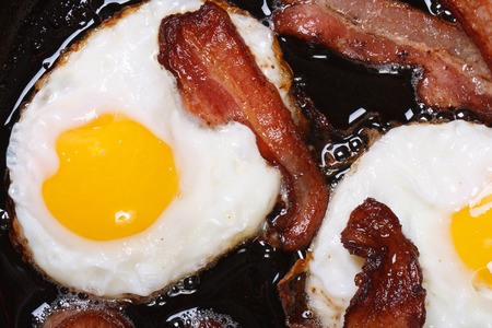whole food: fried eggs with bacon in a pan close-up. top view