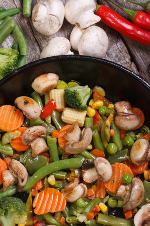 fried mushrooms with vegetables in a frying pan on the table. closeup. vertical. view from above.   photo