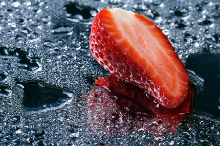 half of fresh strawberries with water drops close-up. horizontal. macro  photo