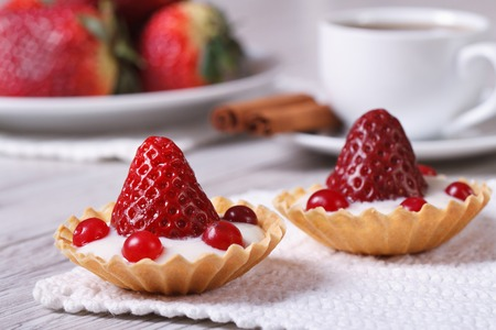 two tartlets with strawberries, cranberries and cream on the table. horizontal. close-up  photo