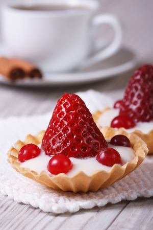two tartlets with strawberries, cranberries and cream on the table. vertical. close-up  photo