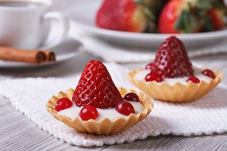 Two delicious fresh strawberry tarts, cranberry and cream on the table. horizontal. close-up   photo