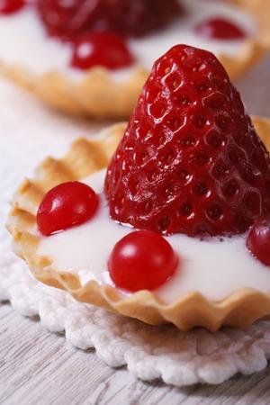brightest: Tartellette con fragole, mirtilli e crema close up sul tavolo. Macro verticale Archivio Fotografico