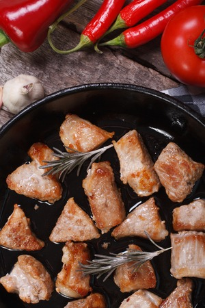 Pieces of fried pork in a frying pan with rosemary and vegetables. view from above. vertical. close-up  photo