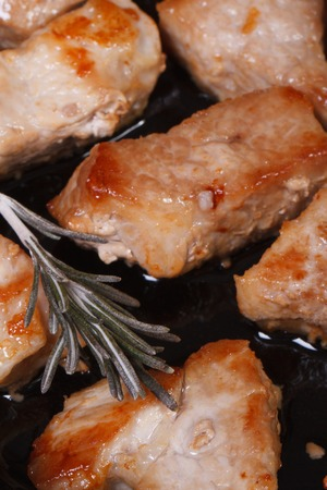 Pieces of fried pork in a frying pan with rosemary macro. view from above. vertical. close-up  photo