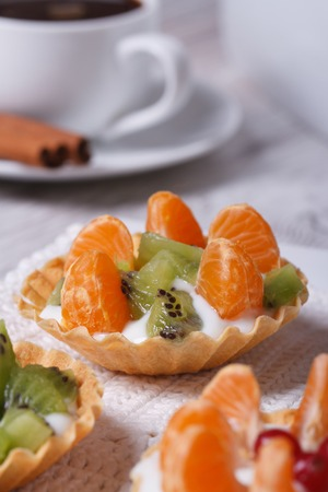 dessert fruit tartlets with mandarin, kiwi and coffee on the table close-up vertical  photo