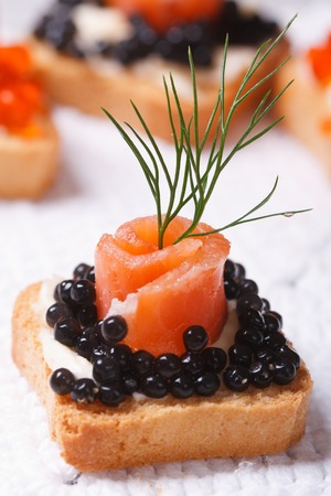Canapes with black sturgeon caviar and salmon fish. macro. vertical  photo