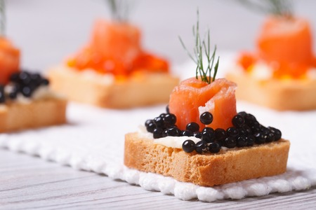 fine wood: Canapes with black sturgeon caviar, smoked salmon and dill. macro. horizontal  Stock Photo