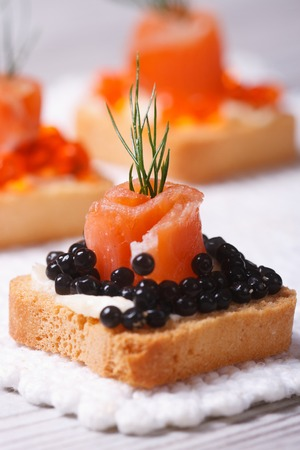 Canapes with black sturgeon caviar, smoked salmon and dill. macro. vertical  photo