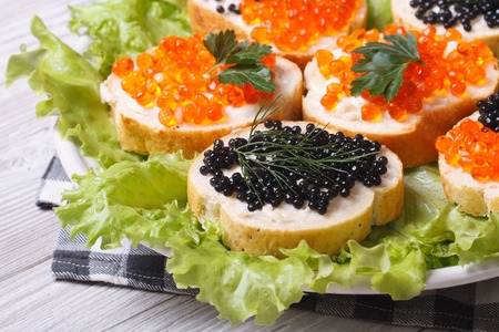 Sandwiches with red and black fish caviar with lettuce closeup horizontal  photo