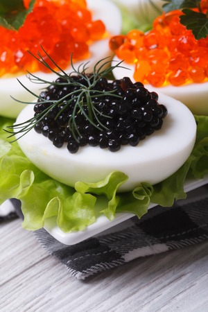 Chicken eggs with red and black fish caviar and lettuce closeup vertical  photo