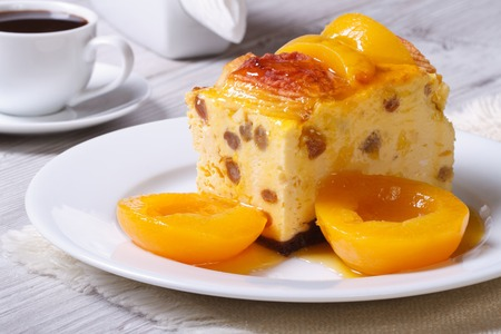 cheese casserole with raisins and peaches on a white plate and coffee on the table  photo