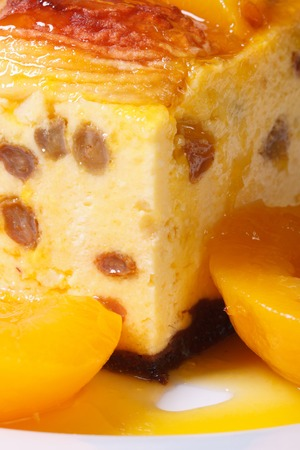 cheese casserole with raisins and peaches on a white plate macro vertical   photo