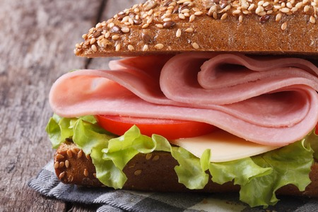 Sandwich with ham, cheese, lettuce and tomatoes on an old table macro. horizontal  Stock Photo