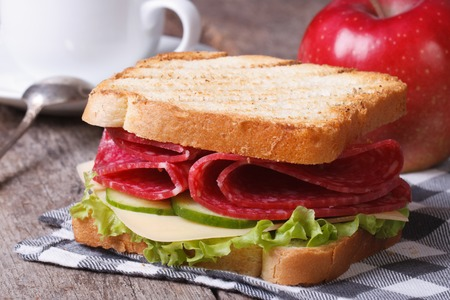 Breakfast: toast with salami, coffee, red apple on the table closeup horizontal   photo