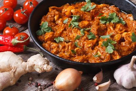 Hähnchen in Curry-Sauce in einer Pfanne mit den Zutaten auf dem alten Schreibtisch