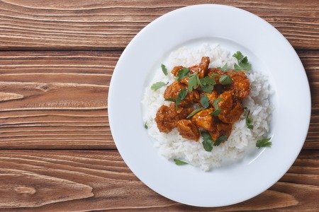 Chicken curry with rice and cilantro on a plate horizontal top view