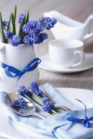 Festive table setting with blue flowers closeup. vertical  photo