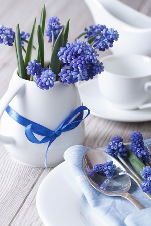 Elegant table setting with beautiful blue flowers muscari vertical   photo