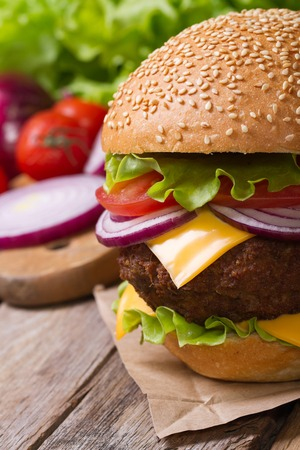 Fresh hamburger with meat and cheese on the table against the background of ingredients   photo