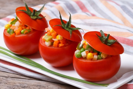 Fresh tomatoes stuffed with vegetable salad on the plate closeup horizontal  photo