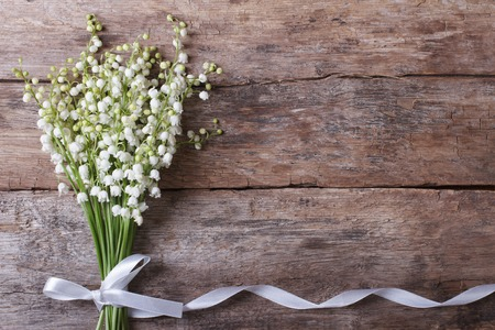 lily of the valley: Beautiful floral frame with lilies of the valley flowers on old wooden table. horizontal  Stock Photo