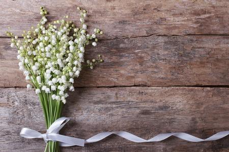 flores de cumpleaños: Hermoso marco floral con lirios de los valles florece en mesa de madera vieja. horizontal