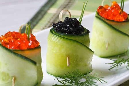 cucumber rolls filled with red and black caviar on a white plate closeup   photo