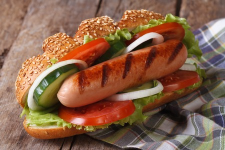 hotdog sandwiches: Hot dog with sausage and vegetables close up on an old table  Stock Photo