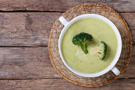 broccoli: Cream soup of broccoli on the table close-up. horizontal top view