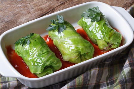 Rolls of young cabbage stuffed with rice and meat in tomato sauce closeup. top view  photo
