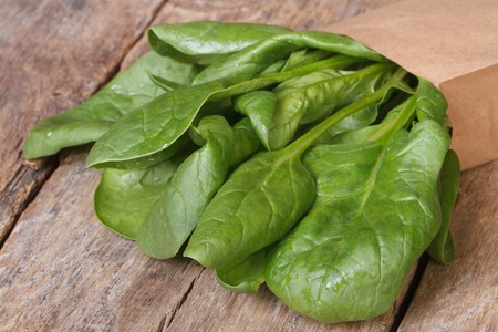 Fresh spinach in a paper packing on the table closeup  photo