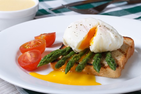 Toast with asparagus and poached egg on a white plate. horizontal  photo