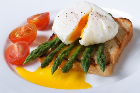 Toast with asparagus, poached egg and tomato on a white plate closeup. horizontal   photo
