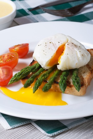 Toast with asparagus, eggs Benedict and tomato on white plate closeup. vertical   photo