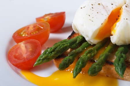 Toast with asparagus, egg Benedict and tomatoes on a white plate macro. horizontal   photo